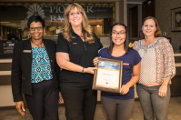 Carolyn Bell, Denise Wilson and Jessica Ponce award Aziah Spicer with her Teller II certificate