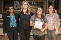 Carolyn Bell, Denise Wilson and Jessica Ponce award Amanda Lucero with her Teller II certificate