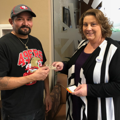 David Mota of Carlsbad receives his gift card from Beth Beene, Team Pioneer