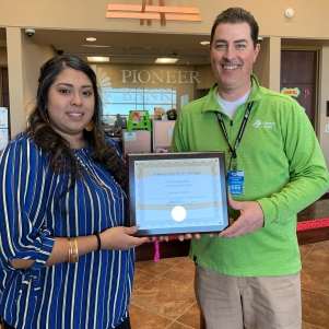 Stephanie Medina receives her 5-year certificate from Christopher Palmer, President